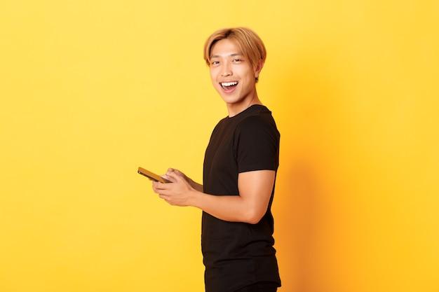 携帯電話を使用して満足の笑みを浮かべて、黄色の壁で頭を回して、黒の衣装でハンサムなスタイリッシュなアジアの男の肖像