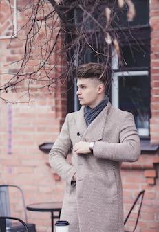 エレガントな秋のコートを屋外でハンサムなスタイリッシュな男の肖像