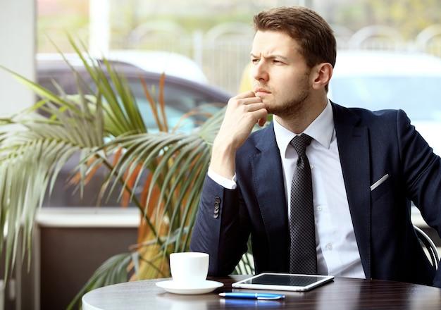 잘생긴 성공한 남자의 초상화는 커피를 마시고 커피숍에 앉아 있는 디지털 태블릿 화면을 바라보고, 비즈니스 남자는 아침 식사를 합니다.