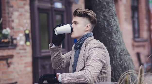 成功したハンサムな男の肖像通りのコーヒーに座ってコーヒーを飲む