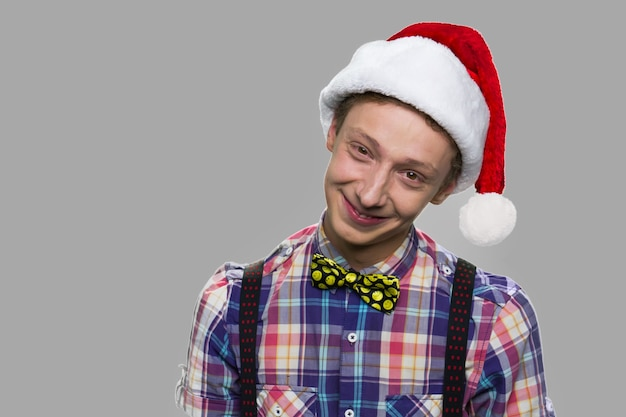 Chistmas 모자에 잘 생긴 십 대 소년의 초상화입니다. 카메라를보고 산타 모자에 친절 한 십 대 남자. 크리스마스 시간 개념입니다.