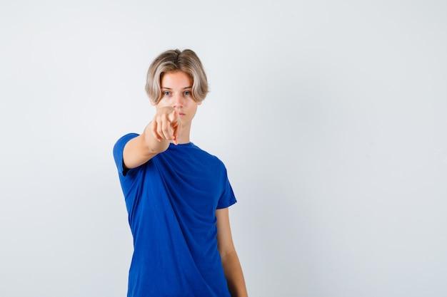 파란색 티셔츠를 입고 앞을 가리키고 자신감 넘치는 앞모습을 바라보는 잘생긴 10대 소년의 초상화