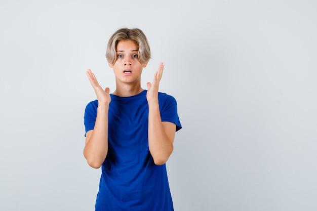 파란색 티셔츠에 항복 제스처를 보이고 겁에 질린 정면을 바라보는 잘생긴 10대 소년의 초상화