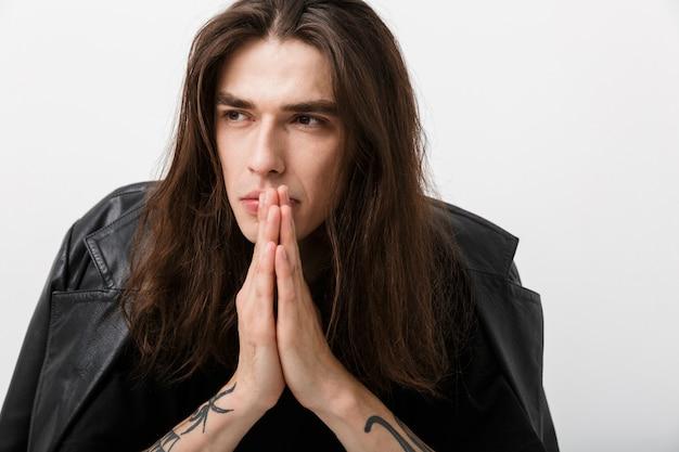 脇を見て、白で手のひらを一緒に保持している泡のジャケットを着て長い髪のハンサムな思考の男の肖像画