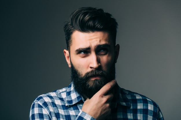 Портрет красивого думающего молодого человека, изолированного на серой стене