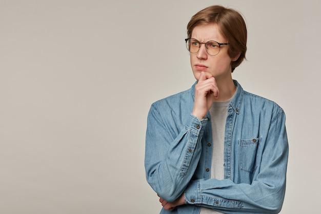 금발 머리를 가진 잘 생기고, 사려 깊은 남자의 초상화. 데님 셔츠와 안경 착용. 턱을 만져. 감정 개념. 회색 벽 위에 고립 된 복사 공간에서 왼쪽을보고