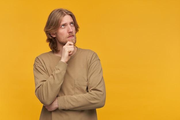 金髪の髪型とあごひげを持つハンサムで思いやりのある男性の肖像画。ベージュのセーターを着ています。あごに触れる。黄色い壁に隔離されたコピースペースで夢のように右を見て