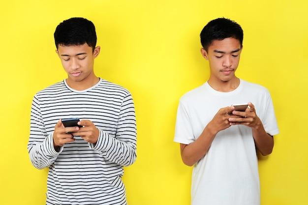 노란색 배경에 격리된 휴대전화를 보고 있는 잘생긴 두 젊은 아시아 남성의 초상화