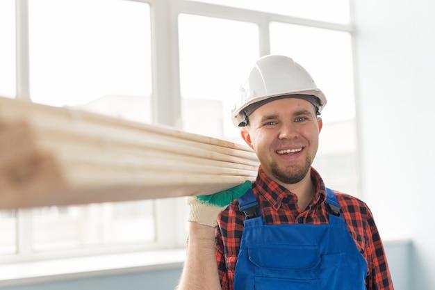 Портрет красивого белого мужчины-строителя, смеющегося перед окном в белом шлеме