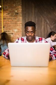 ラップトップに取り組んでいるカフェに座っているハンサムな若いアフロアメリカンの男のポートレート