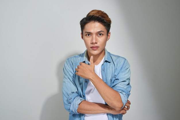 스튜디오에서 포즈를 취하는 잘생긴 젊은 아시아 남자의 초상화.