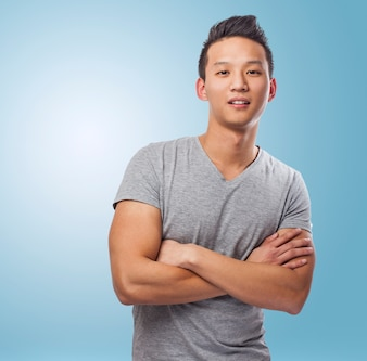 Portrait of handsome young asian man standing over blue backgrou