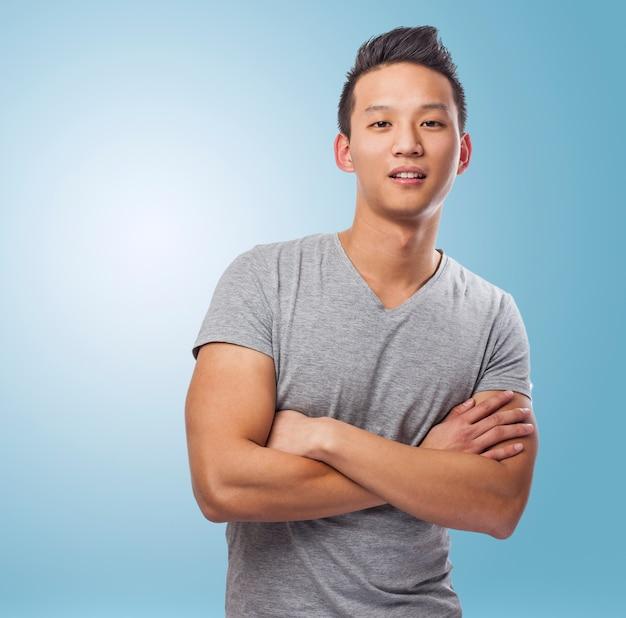 青backgrouの上に立ってハンサムな若いアジア人の肖像画