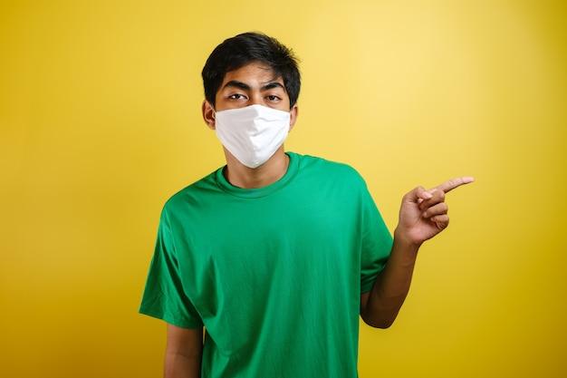 サイドコピースペースに彼の指を指している医療保護マスクを身に着けているハンサムな若いアジア人の肖像画。黄色の背景に対して、コロナウイルスcovid-19と戦う概念