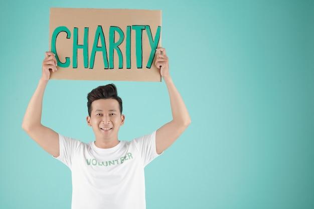 Портрет красивого молодого азиатского мужчины с плакатом, продвигающим благотворительную акцию