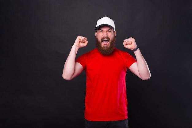 Портрет красивого молодого бородатого мужчины празднует победу с поднятыми кулаками и кричит