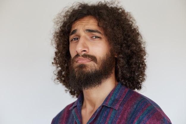 カジュアルなストライプのシャツでポーズをとって、眉を眉をひそめ、額にしわを寄せる暗い巻き毛のハンサムな若いひげを生やした男の肖像画