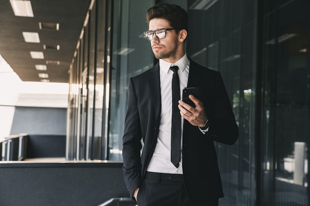 유리 건물 밖에 서서 휴대 전화를 들고 공식적인 양복을 입은 잘 생긴 젊은 사업가의 초상화