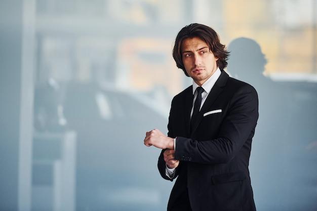 黒のスーツとネクタイのハンサムな青年実業家の肖像画。