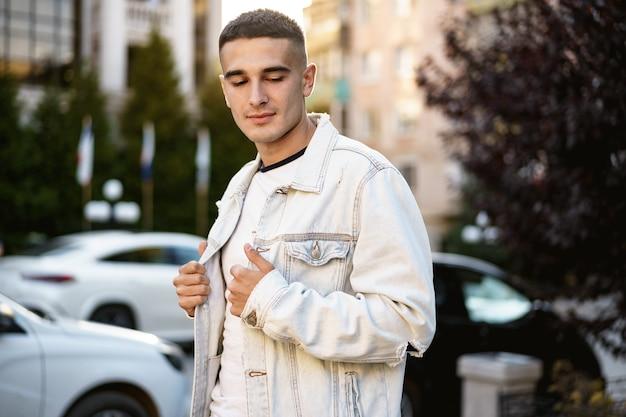 通りを歩いているハンサムな若いカジュアルな男の肖像画
