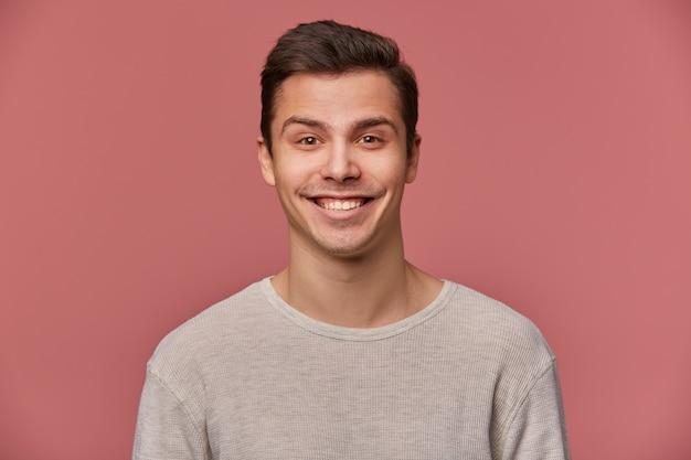 ハンサムな若い陽気な男の肖像画は、空白の長袖を着て、幸せな表情でカメラを見て、ピンクの背景の上に立っています。