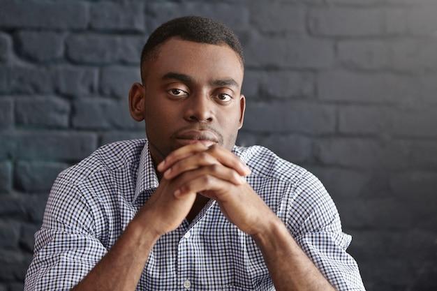 物思いに沈んだ思慮深い表情のフォーマルな服装のハンサムな若い浅黒い男性の肖像画