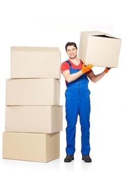 Портрет красивого молодого доставщика с бумажными коробками, изолированными на белой стене