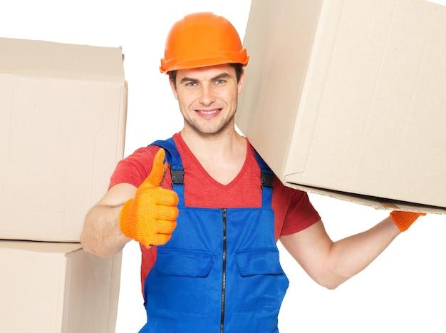 Портрет красивого молодого доставщика с бумажными коробками, показывающими палец вверх, изолированные на белом