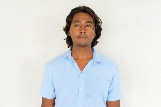 평범한 배경에 대해 잘생긴 젊은 인도 남자의 초상화