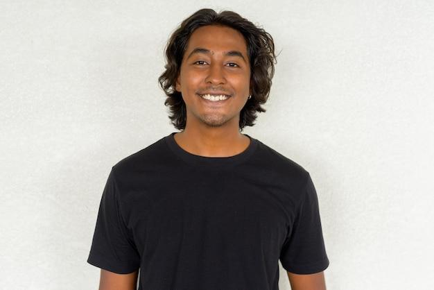 평범한 배경에 웃고 있는 잘생긴 젊은 인도 남자의 초상화