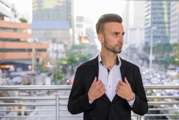 スーツを着て街の屋外でハンサムな若いイタリア人実業家の肖像画