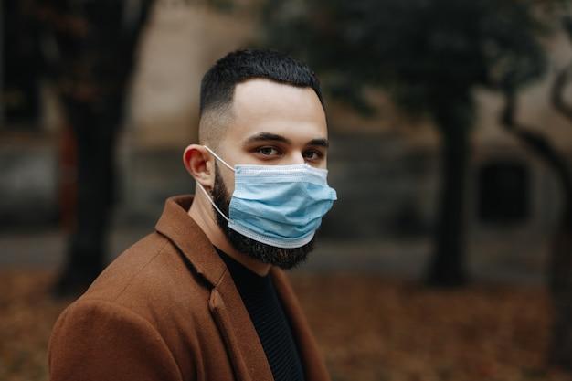의료 얼굴 마스크에 거리에 서있는 베이지 색 코트를 입은 잘 생긴 젊은 남자의 초상화. 가 공원의 배경을 흐리게합니다.