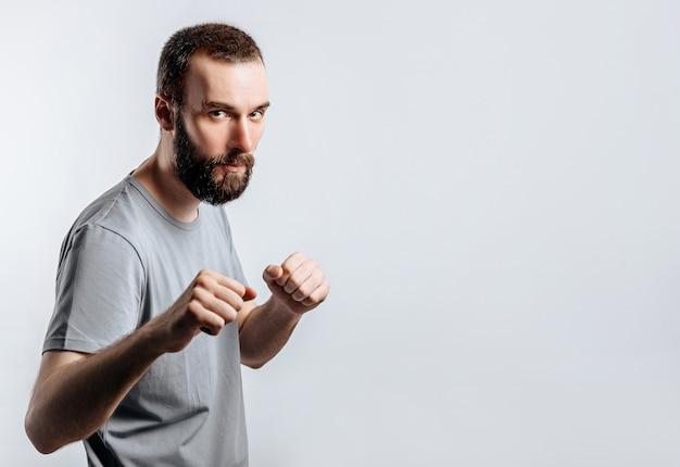 拳を保持し、白い表面でボクシングのカメラを見ながら眉をひそめているハンサムな若い男の肖像画