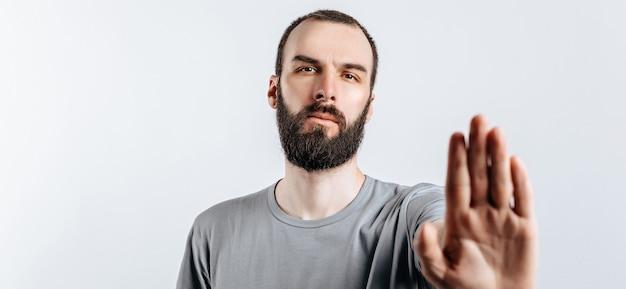 Портрет красивого молодого человека, нахмурившегося, глядя в камеру, держа руку напротив и говоря жест стоп на белом фоне с пространством для макета рекламы