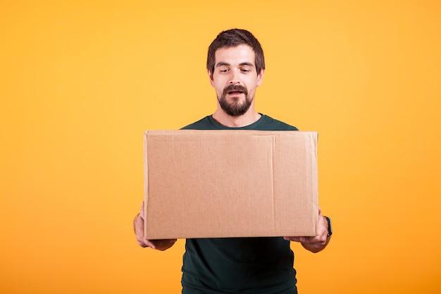 手に箱を持っているハンサムな若い男の肖像画。黄色の背景に配達人