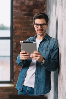 Портрет красивый молодой человек, проведение цифровой планшет в руках