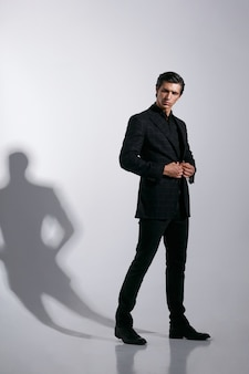 白い背景で隔離の黒のスタイリッシュなスーツのハンサムな若い男の肖像画。フルレングスの画像。