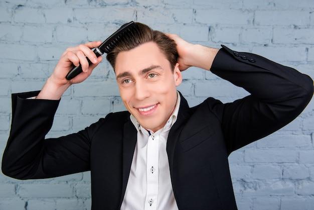 Портрет красивого молодого человека в черном костюме, расчесывающего волосы