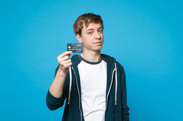 青い壁に分離されたクレジット銀行カードを保持しているカジュアルな服を着たハンサムな若い男の肖像画。人々の誠実な感情、ライフスタイルのコンセプト。