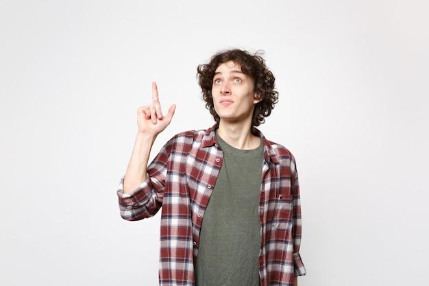 スタジオの白い壁の背景に分離された素晴らしい新しいアイデアで人差し指を持ち上げるカジュアルな服を着たハンサムな若い男の肖像画。人々の誠実な感情のライフスタイルの概念。コピースペースをモックアップします。
