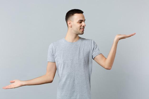 カジュアルな服を着たハンサムな若い男の肖像画が広がり、見て、手を脇に向ける