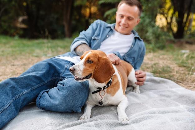 그의 개 강아지와 함께 공원에서 담요에 앉아 데님 옷에 잘생긴 젊은 남자의 초상화