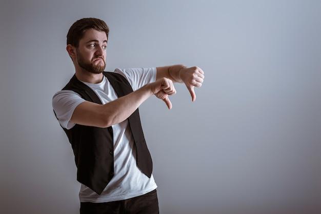Портрет красивого молодого человека в белой рубашке, показывая пальцы руки вниз на сером фоне.