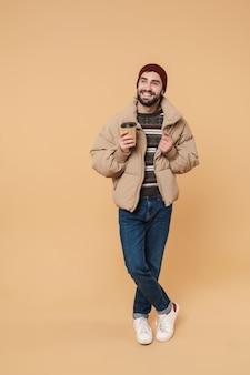 Портрет красивого молодого человека в зимней куртке и шляпе, улыбающегося, держа чашку кофе, изолированную на бежевом