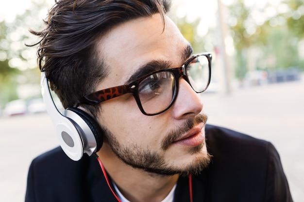 Портрет красивого молодого человека, слушающего музыку на улице.