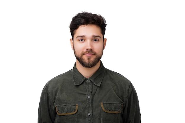 흰색 벽 배경 위에 서 있는 카메라를 바라보는 잘생긴 젊은 남자의 초상화