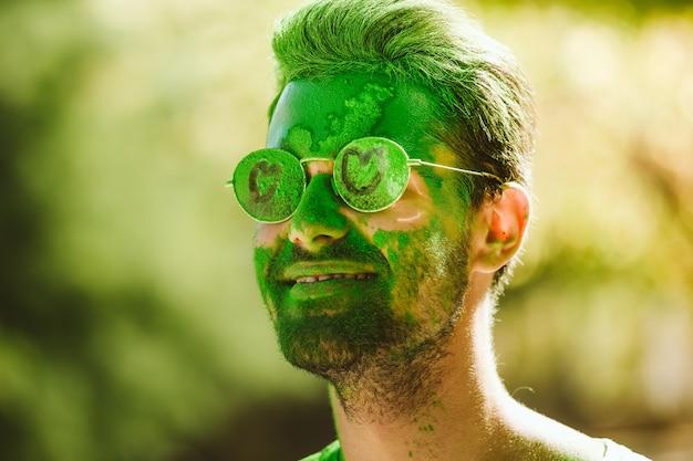 Портрет красивого молодого человека, играющего в парке на фестивале цветов холи.
