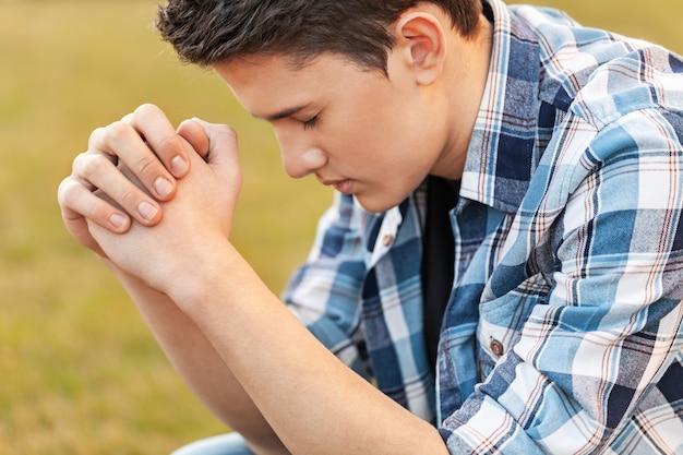 기도하는 잘생긴 젊은 남자의 초상화