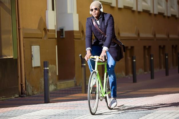 거리에서 자전거를 타는 잘생긴 젊은 남자의 초상화.