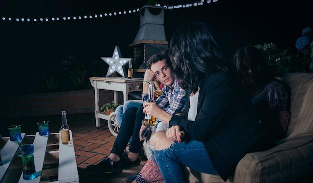 野外パーティーでビールを持っている女性の友人と座って話しているハンサムな若い男の肖像画。友情とお祝いのコンセプト。